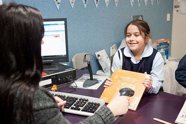 St Josephs Catholic Primary School Belmore - student borrowing book from the library